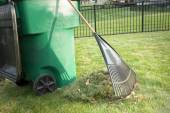 Raking up grass cuttings in spring — Stock Photo