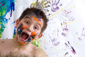 Excited happy little boy doing finger painting — Stock Photo