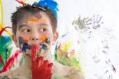 Thoughtful creative little boy covered in paint — Stock Photo