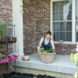Woman tending to newly potted plants on her patio — Stock Photo #72323651