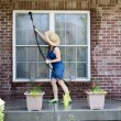 Housewife washing the windows of her house — Stock Photo #72323901