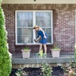 Woman washing the exterior windows of a house — Stock Photo #72323987