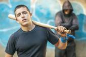 Aggressive teenager with a baseball bat on building background — Stock Photo