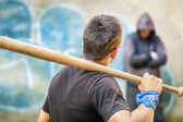 Aggressive teenager with a baseball bat against man at outdoor — Stock Photo