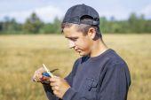 Tiener met een mes snijdt de tak op het veld — Stockfoto