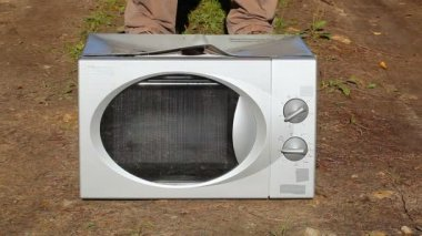 Man with sledge hammer destroying microwave oven — Stock Video