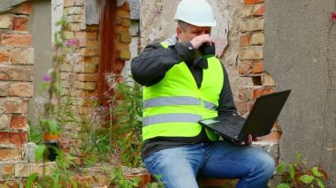 Construction Engineer working with PC and drinking tea — Stock Video