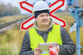 Railway engineer with tablet PC near warning signs — Stock Photo