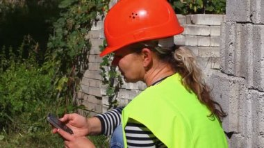 Woman-builder with the cell phone — Stock Video