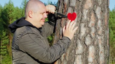 Sorrowful man holding knife and fabric heart near the tree — Stock Video