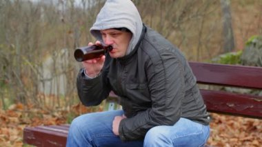 Sorrowful man drink beer from bottle in the park — Stock Video