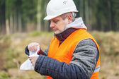Forest engineer destroying sensitive documents in the forest — Stock Photo