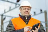 Electrical Engineer with tablet PC in the electric substation — Stock Photo
