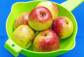 Red apples in green sieve on blue background — Stock Photo