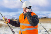 Electrical Engineer talking on cell phone near tensioner — Stock Photo
