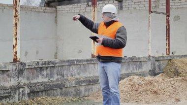 Ingénieur civil, parler au téléphone cellulaire près d'un édifice inachevé — Vidéo