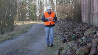 Worker with tablet PC on road near at piles of stones — Vídeo de stock