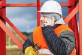 Worker with cell phone near metal structures — Stockfoto