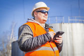 Engineer with tablet PC with oil tank in the background — Stock Photo