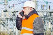Electrical engineer talking on cell phone at power station — Stock Photo