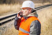Railway employee talking on cell phone near railway — Stock Photo