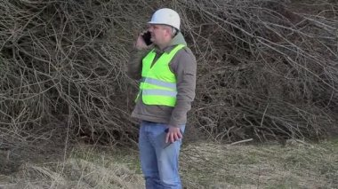 Forest engineer talking on cell phone near pile of twigs — Stock Video