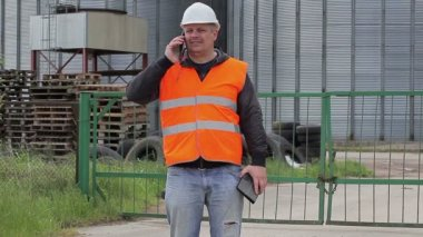 Engineer with cell phone near the factory — Stock Video