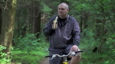 Man eating bananas on bicycle in the park — Stock Video