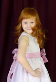 Portrait of red-haired girl on a red background — Stockfoto