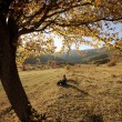Colorful autumn tree at sunset with woman sitting and contemplating nature — Stock Photo #54319415