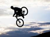 Silhouette of a man doing a jump with a bmx bike — Stock Photo