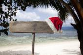 Wooden signboard with Christmas hat on tropical beach  — Foto Stock