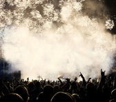 New Year concept - cheering crowd and fireworks — Stock Photo