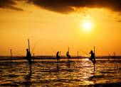 Silhouettes of the traditional stilt fishermen at the sunset nea — Stock Photo