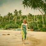 Woman walking on tropical beach - retro style photo — Stock Photo #74969545