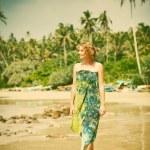 Woman walking on tropical beach - retro style photo — Stock Photo #74969585