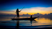 Beautiful sky and Silhouettes of fisherman at the lake, Thailand — Stock Photo