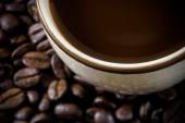 Close up of blur roasted coffee beans and hot coffee. — Stock Photo