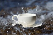 Refreshments water and coffee cup on the rocks at the waterfalls — Stock Photo