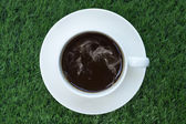 Coffee cup on artificial grass — Stock Photo