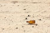 Empty bottle in desert — Stock Photo