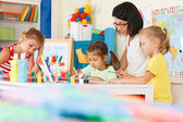 Children with teacher draw in the classroom — Stock Photo