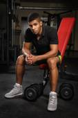 Young man sitting on bench at gym — Stock Photo