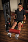 Young man doing legs extensions workout in gym — Stock Photo