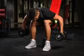 Young man doing Seated Bent Over Dumbbell Reverse Fly workout in gym — Stock Photo