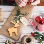 Woman wrapping cool christmas gift — Stock Photo #57763661