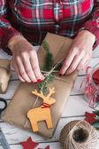 женщина, обертывающая прохладный рождественский подарок — Стоковое фото