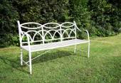 White bench in green garden — Stockfoto