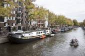 Small boat passing houseboats in brouwersgracht — Stock Photo