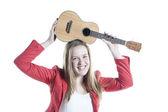 Teenage girl holds ukelele in studio against white background — Stock Photo